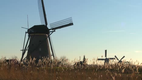 A-slow-pan-across-to-windmills-rising-from-the-grass-in-Holland