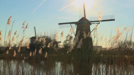 A-slow-tilt-up-to-windmills-standing-along-a-canal-in-Holland