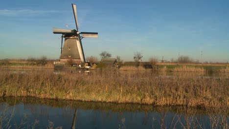 A-windmill-rises-above-a-canal-and-grass-in-Holland