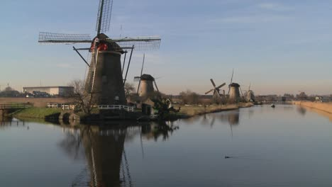 A-boat-moves-along-a-canal-in-Holland-with-windmills-nearby