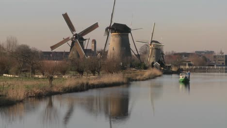 A-boat-moves-along-a-canal-in-Holland-with-windmills-nearby-1