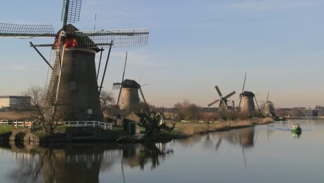 A-boat-moves-along-a-canal-in-Holland-with-windmills-nearby-2