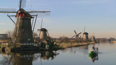 A-boat-moves-along-a-canal-in-Holland-with-windmills-nearby-3