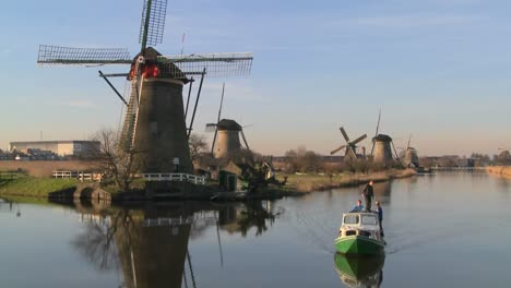 A-boat-moves-along-a-canal-in-Holland-with-windmills-nearby-4