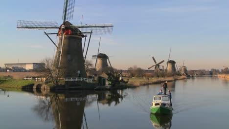 Ein-Boot-Fährt-Einen-Kanal-In-Holland-Mit-Windmühlen-In-Der-Nähe-4