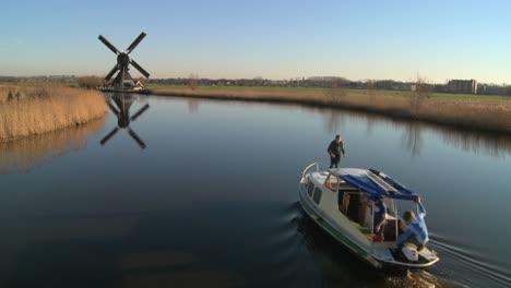 A-boat-moves-along-a-canal-in-Holland-with-windmills-nearby-5