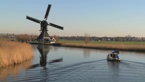 A-boat-moves-along-a-canal-in-Holland-with-windmills-nearby-6