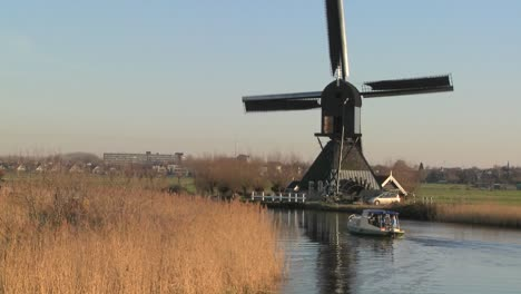 A-boat-moves-along-a-canal-in-Holland-with-windmills-nearby-7