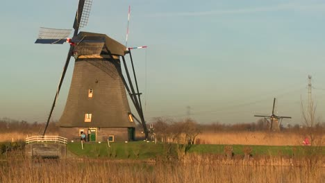 A-woman-rides-a-bicycle-past-a-windmill-in-Holland