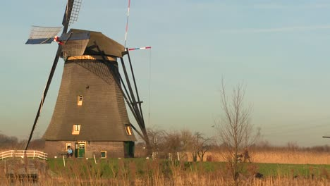 A-woman-pushes-a-baby-carriage-along-a-path-near-a-windmill-in-Holland