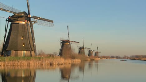 Windmills-line-up-perfectly-along-a-canal-as-a-small-boat-crosses-in-the-distance
