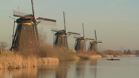 Windmills-line-up-perfectly-along-a-canal-as-a-small-boat-crosses-in-the-distance-1