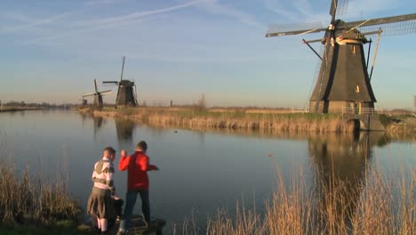 -children-play-beside-a-canal-and-windmills-in-Holland