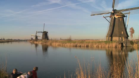 Children-play-in-front-of-windmills-along-a-canal-in-Holland