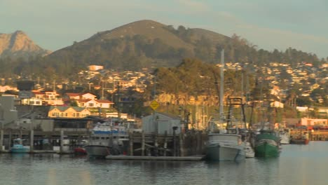 A-pan-across-the-small-Central-California-town-of-Morro-Bay-with-fishing-boats-in-the-harbor
