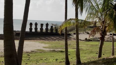 Easter-Island-statues-stand-in-a-long-row-on-a-distant-beach