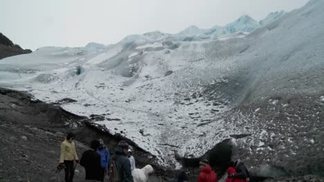 Hikers-gather-at-the-base-of-a-glacier-for-a-trek
