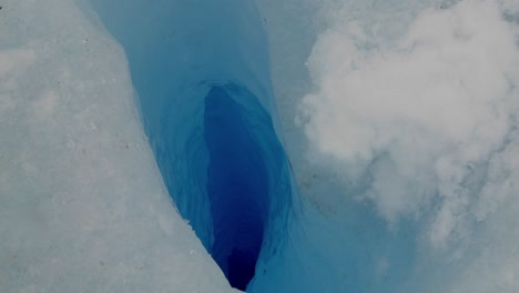 A-zoom-into-a-deep-blue-hole-in-a-glacier