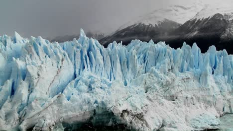 The-spiked-tops-of-a-glacier-stand-against-rugged-mountains