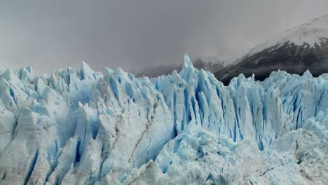 The-spiked-tops-of-a-glacier-stand-against-rugged-mountains-1