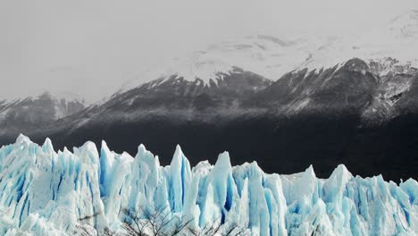 The-spiked-tops-of-a-glacier-stand-against-rugged-mountains-2