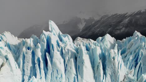 The-spiked-tops-of-a-glacier-stand-against-rugged-mountains-4