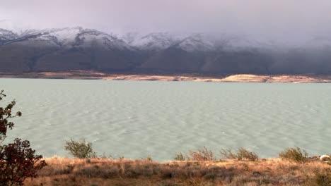 A-glacial-river-flows-beneath-foggy-mountains