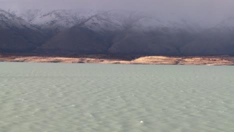 A-glacial-river-flows-beneath-foggy-mountains-1