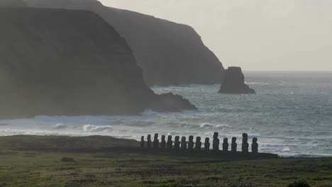 Easter-Island-statues-stand-in-the-distance-against-the-Pacific-Ocean