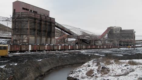 An-abandoned-mine-with-ore-rail-cars-in-the-foreground