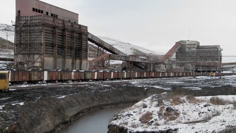 Pan-across-an-abandoned-mine-with-ore-rail-cars-in-the-foreground
