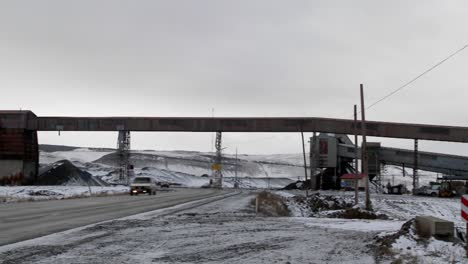 Pan-across-an-old-abandoned-mine-in-winter-with-traffic-passing-on-a-road