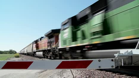 A-freight-train-speeds-past-a-gated-railroad-crossing