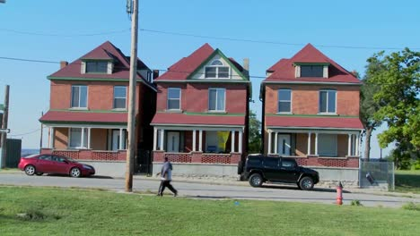 Three-tenement-houses-stand-together-in-an-urban-section-of-the-city