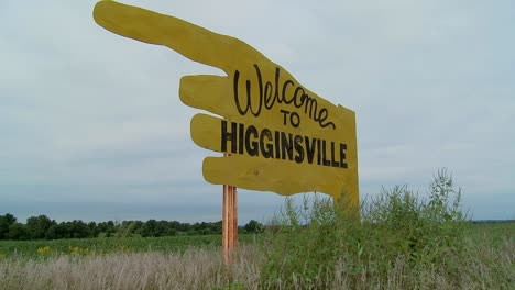 A-large-yellow-sign-points-to-Higginsville-Missouri-from-a-farm-field