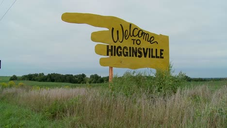 A-large-yellow-sign-points-to-Higginsville-Missouri-from-a-farm-field-1