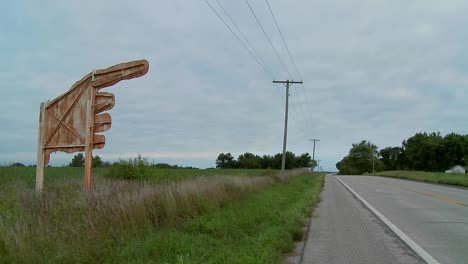 A-large-yellow-sign-points-to-Higginsville-Missouri-from-a-farm-field-2