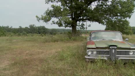 Pan-to-an-old-abandoned-Ford-Edsel-sitting-in-a-field