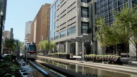A-rapid-transit-train-moves-quickly-through-downtown-Houston-with-fountains-dancing-4