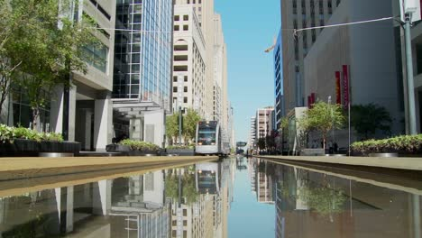 A-rapid-transit-train-moves-quickly-through-downtown-Houston-with-fountains-dancing-5