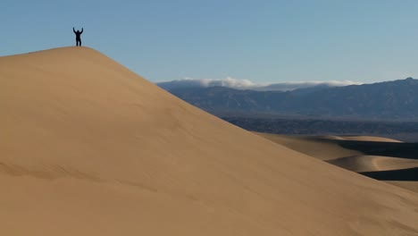 A-person-jumps-up-and-down-on-a-desert-dune-to-symbolize-victory-or-achievement-of-a-goal