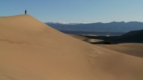 A-person-jumps-up-and-down-on-a-desert-dune-to-symbolize-victory-or-achievement-of-a-goal-1