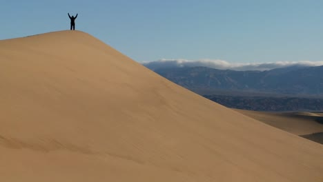A-person-jumps-up-and-down-on-a-desert-dune-to-symbolize-victory-or-achievement-of-a-goal-2