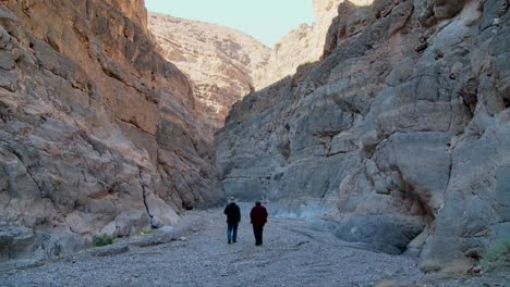 A-senior-man-and-woman-hike-in-a-canyon-in-Death-Valley
