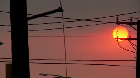 A-orange-ball-of-sun-sets-behind-power-lines-during-fire-season-in-California