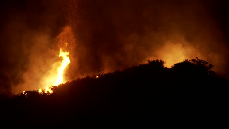 Firefighters-battle-a-raging-California-wildfire-at-night-by-performing-a-water-drop-from-an-aerial-tanker