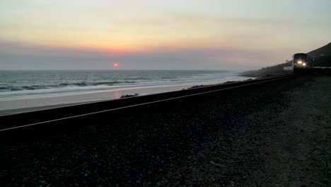 Beautiful-shot-of-an-Amtrak-train-passing-by-a-California-beach-at-sunset