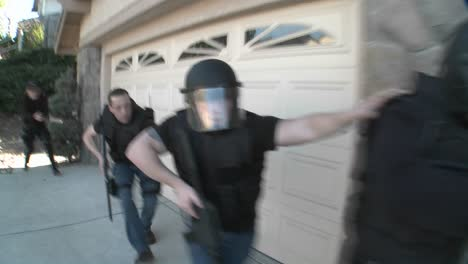 DEA-or-SWAT-officers-with-arms-drawn-perform-a-drug-raid-on-a-house