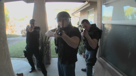 DEA-or-SWAT-officers-with-arms-drawn-perform-a-drug-raid-on-a-house-1