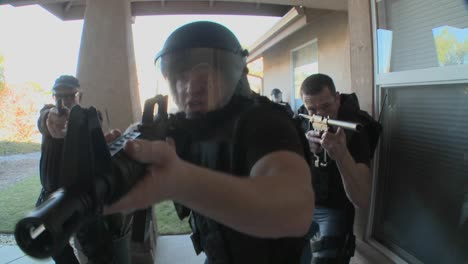 DEA-or-SWAT-officers-with-arms-drawn-pound-on-the-door-before-performing-a-drug-raid-on-a-house
